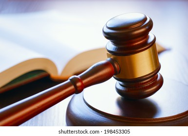 brown gavel and open book on a wooden table of the law in the courtroom