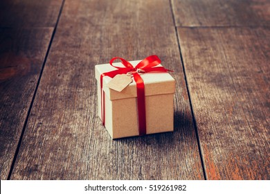Brown gift box and red ribbon with tag on wood background with space.