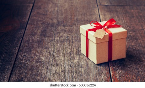 Brown gift box and red ribbon with tag on wood background with space. Vintage gift box on wooden board with space for text.