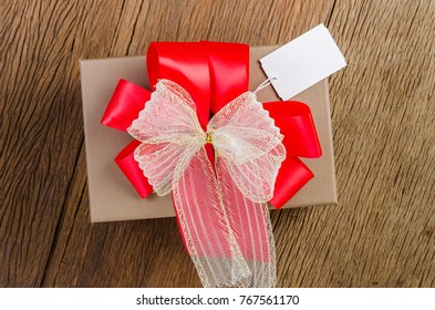 brown gift box with white bow with tag on wooden board background