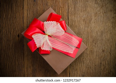 Brown gift box with white and red bow on wooden board background