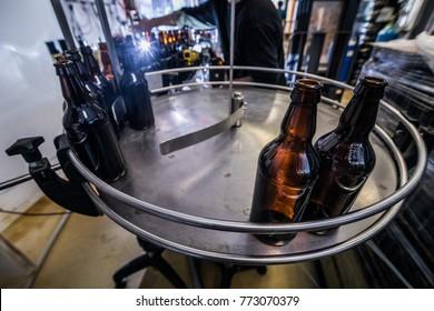 Brown glass beer bottles on conveyor for filling and bottling.