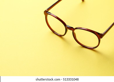 Brown glasses on yellow background