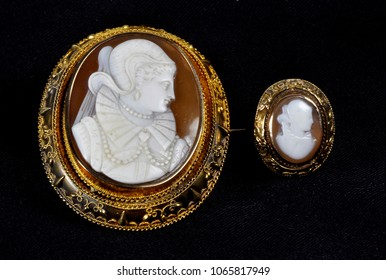 Brown and Gold Antique Cameo Broach with matching ring on a black background