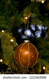 Brown golden christmas ball hanging in a tree