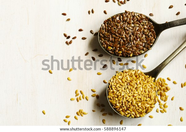 Brown and golden flax seeds in spoons