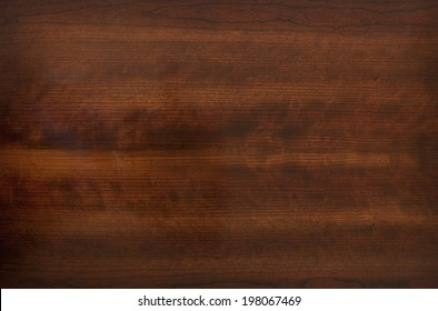 The brown, grainy appearance of a wooden surface.
