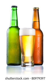 Brown and green bottles full of condensate and covered with a glass of fresh cold beer isolated on a white background