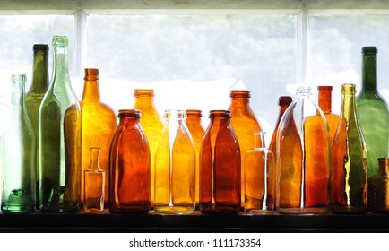 Brown and green old glass bottles on windowsill, with curtain. Closeup, daylight.
