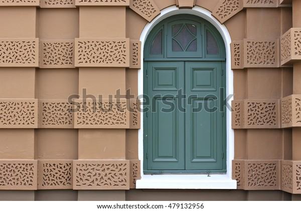Brown and green wood siding Windows.