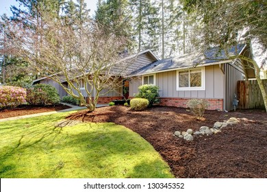 Brown grey house exterior with spring landscape. One story building.