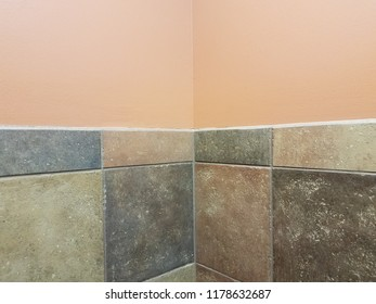 brown and and grey tiles and peach wall in bathroom corner