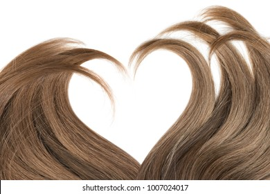 Brown hair in shape of heart on white background. Hair care concept
