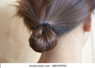 Brown hair tied with a rubber band