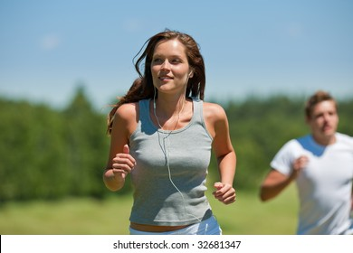 Brown hair woman with headphones jogging, man in background, shallow DOF