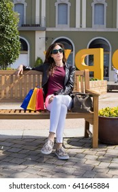 brown hair woman with white jeans, red shirt, leather blazer jacket and sunglasses sitting in wooden bench, at street, with shopping bags and purse