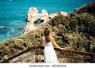 Brown haired girl wearing white dress looking out on the ocean. Lagos, Algarve Coast, Portugal