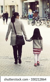 A brown haired is mom taking a child to a kindergarten. The girl is walking happily on the way with a red striped skirt. The mom is carrying a black bag. Image has a vintage effect applied.