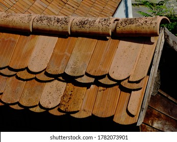 brown half round ridge clay roof tiles over entrance gate. curved ridge tiles on top of flat shingles. bright summer light. blurred yellow stucco wall background. abstract view.