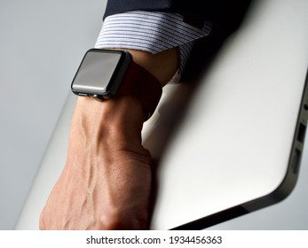 Brown hand wearing black smart watch and carrying a sleek silver laptop going to a work remotely