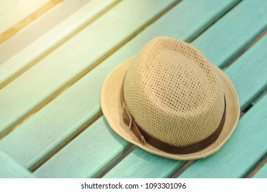 Brown hat on green wooden bench in the park