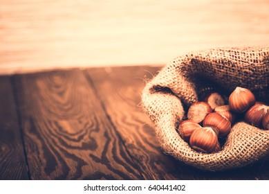 Brown hazel nut. Healthy organic snack hazelnut. Group of food ingredient. Filbert nutshell seed. Natural protein fruit macro. Vegetarian nutrition. Burlap textile background.