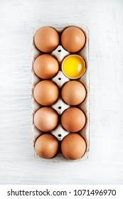 brown hen's eggs one egg yolk visible decorated in a box, rustic food photography on white wood can be used as background