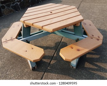 brown hexagon picnic table on cement or pavement