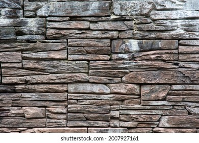 brown horizontal textured wall made of decorative stone with moss and white stains