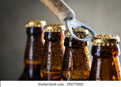 Brown ice cold beer bottles with water drops and old opener