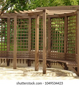 Brown Japanese Style Wooden Rounded Alcove Or Terrace On The Backyard.    Open Veranda In The Garden With Bench. Brown Pergola In The Park.