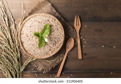 brown Jasmine rice in bamboo basket on dark wood background with copy space, healthy food and diet concept