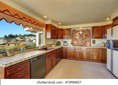 Brown kitchen interior with cabinets, tile counter tops, brick wall, white fridge. Decorated with yellow daffodils in glass vase. Northwest, USA
