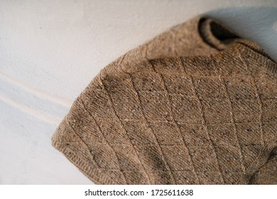 brown knitted woolen scarf lies on a white background