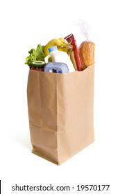 A brown kraft bag full of groceries including, milk, eggs, bread etc