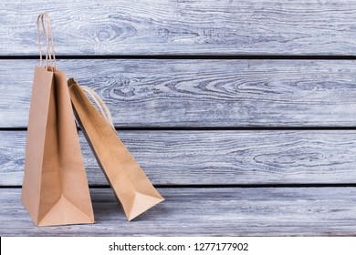 Brown kraft paper bags for gifts. Recycle paper shopping bags on wooden background with text space.