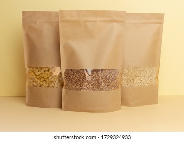 Brown kraft paper doypack bags with Buckwheat, pasta, rice front view on a yellow background. Packaging for foods and goods template mock-up. Packs with windows for weight products.