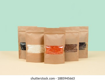 Brown kraft paper doypack bags with groceries front view on a yellow background. Packaging for foods and goods template mock-up. Packs with windows for weight products.