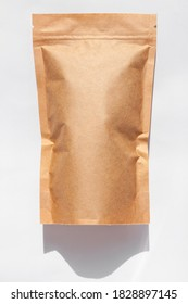 Brown kraft paper pouch bags with coffee beans top view with shadow isolated on white background. Packaging for foods and goods template mockup. Pack with clasp for tea leaves,weight products flat lay
