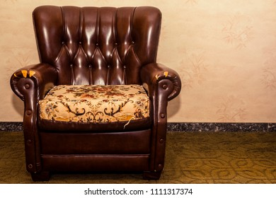Brown leather armchair wthtorn part drapery placed in the empty room. Old furniture for a vintage decoration. Space for text.
