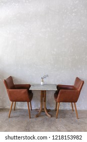 Brown leather armchairs and marble coffee table on gray fresco wall background in a restaurant