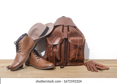 brown leather bag or backpack with brown shoes,hat ,gloves on wooden background
