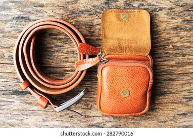 Brown leather bag, box with belt on wood