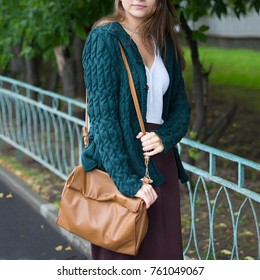 A brown leather bag on a girl's shoulder. Close up.