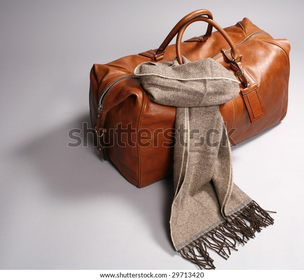 brown leather bag with scarf on grey background