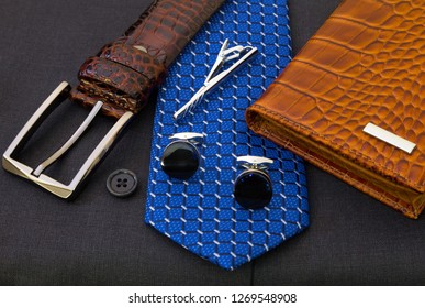 Brown leather belt, blue tie with metal pin and sapphire cuff links, wallet on dark grey waistcoat. Fashion concept
