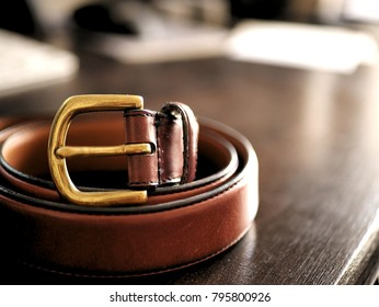 Brown Leather Belt on Dark Wooden Desk