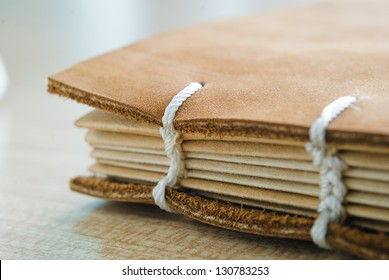 brown leather book cover with white thread book spine