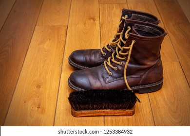 brown leather boots and a shoe brush on a wooden floor