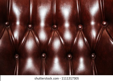 Brown leather cloth sewing with buttons intending for cushioned furniture texture background. Close up of an antique sofa. Graphic resource for a vintage design.